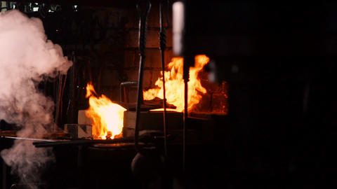 Hardening of the metal by sharp cooling in water. There is steam. The blacksmith Footage