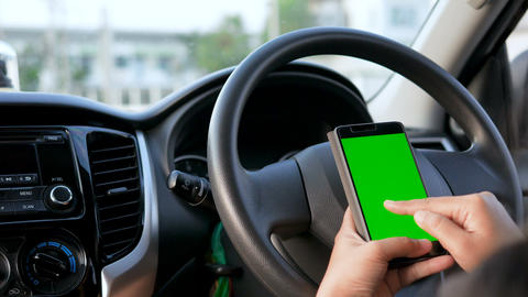 Hands of woman using using smartphone with green screen monitor at interior of SUV car for mobile Live Action