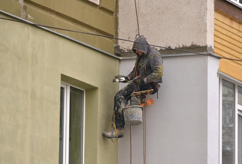 The man works on high-rise works cladding, plastering of the house フォト