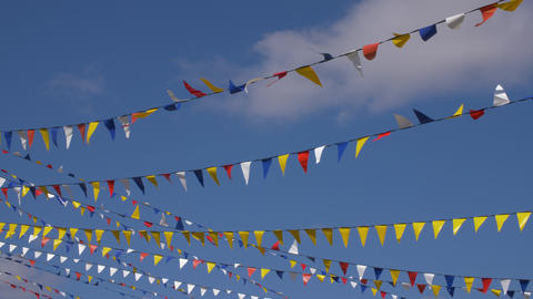Multicolored triangle flags for party waving on wind on blue sky background Footage