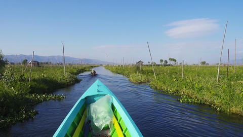 Boat floats among floating gardens on Inle Lake Live Action