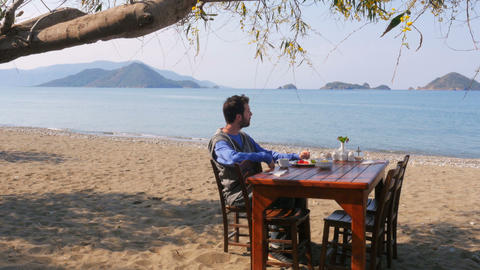 Tourist man eating gorgeous breakfast beach with majestic sea background Footage
