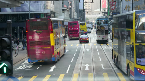 Trams and buses move along a busy road Footage