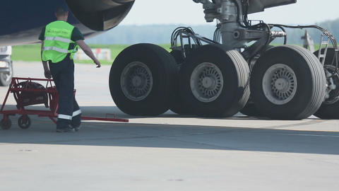 Airport worker installs pads under the chassis of the aircraft parking Footage