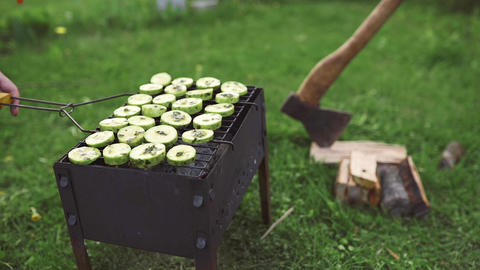 Cooking of the vegetarian barbeque with zucchini in green onion sauce on the hot Live Action