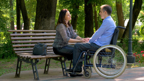 Young man on wheelchair talking with his wife in park GIF