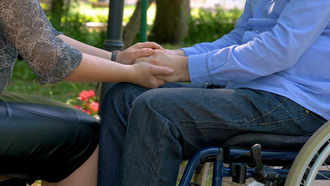 Disabled young man encouraged by his wife outdoors GIF