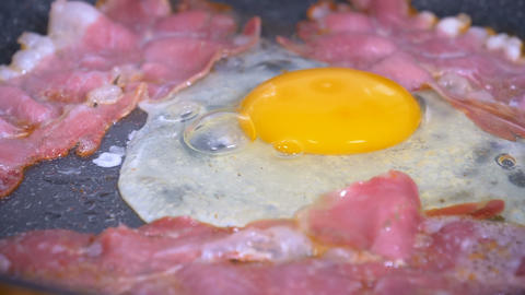 Egg being dropped on fried bacon in slow motion Footage
