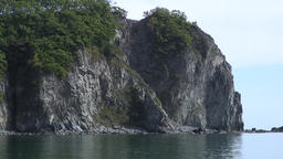 Green stony rocks coastline beach and sea waves water surface in Japan Sea Footage