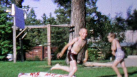 1967: Kids dive into backyard kiddie pool in slow motion Footage