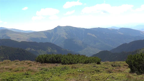 Horizontal panorama over the peaks of forested mountains 0a Footage