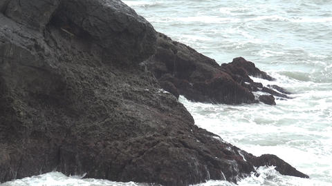 Waves that burst the rocky shore forming foams and bubbles 21 Footage