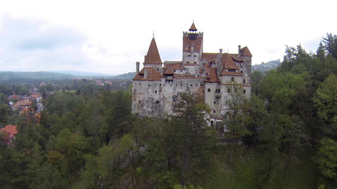 Aerial image of a castle built on a rock that rises drone shot from the thick fo Footage
