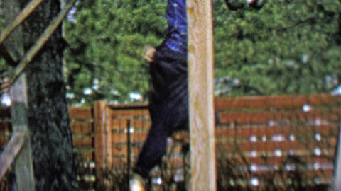 1962: Thug black hooded kid hanging monkey bars outdoor park Footage