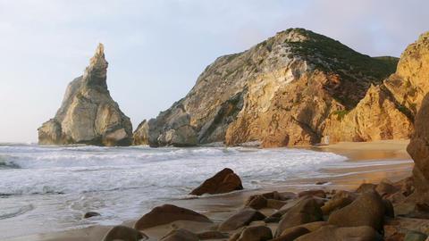 The Ocean Surf on an Empty Beach Between the Cliffs Footage