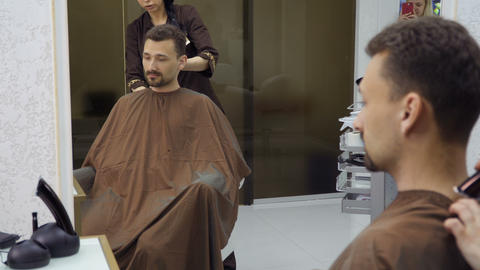 Hairdresser cuts hair of handsome man with electric razor Footage