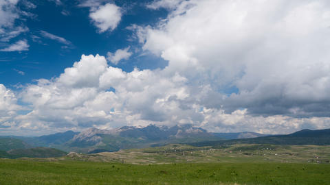 Clouds over the green meadow with majestic mountains in the background Live Action