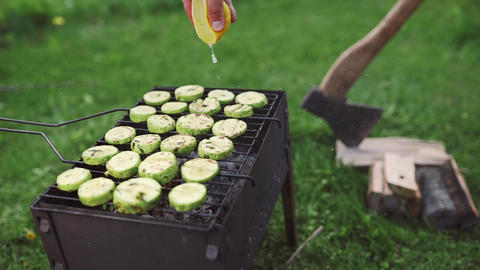 The cook makes vegetarian barbeque with zucchini in green onion sauce on the hot Live Action