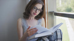 Attractive woman sitting by window and reading Footage