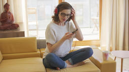 Barefoot woman listening to music on sofa Footage