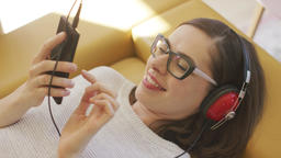 Cheerful woman listening to music and browsing smartphone Footage
