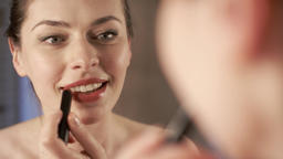 Young woman putting lipstick make-up Footage