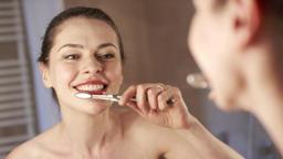 Female looking in mirror and brushing teeth Footage