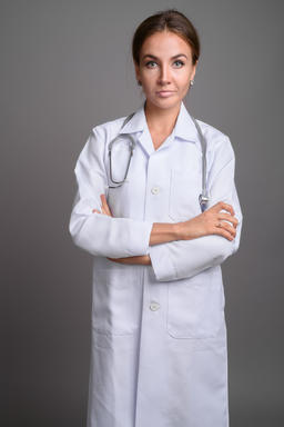 Young beautiful woman doctor against gray background Fotografía