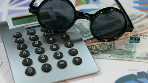 Sun protective hipster glasses lie on the calculator and rubles. Rotation Footage