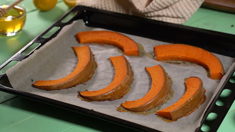 The chef brings a baking sheet with baked pumpkin slices Footage