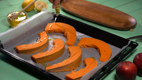 chef pours pumpkin slices with olive oil Footage
