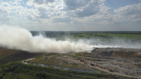 Burning garbage dump pollutes the environment. Strong wind rises toxic smoke of Live Action