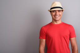 Tourist man wearing hat and red shirt against gray background フォト