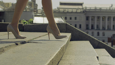 Female legs in high heels stepping down on stairway Footage