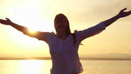 Woman raising arms up at sunset on lake. Female outstretching hands at golden Footage