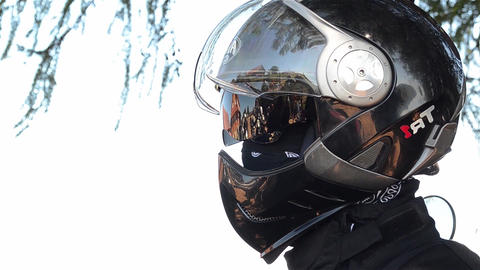 Motorcyclist with a black helmet on his head and black scarf at the neck that si Footage