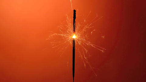 Burning sparkler on an orange background Footage