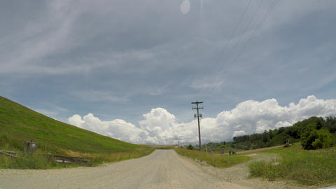 POV wide angle driving on a gravel country road alongside grassland during the 영상물