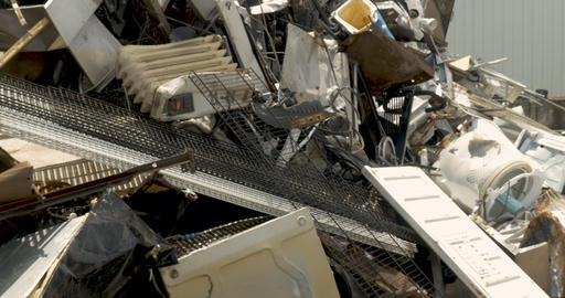 Metal trash being thrown into a pile of recycled metal and appliances at a Footage