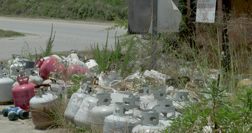 Propane tanks and canisters thrown away in the grass next to a dumpster as a Footage