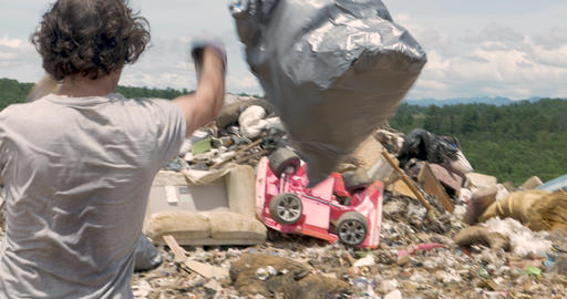 Man throwing a bag of trash and a broken office chair into the landfill Footage