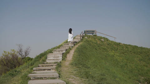 Elegance woman moves up the stairs on green hiil Footage