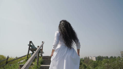 Woman in white dress reach the peak and raise up hands like a winner Live Action