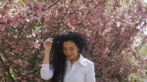 Pretty brunette walk near sakura in slow motion Footage