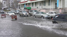 Cars driving on street road over muddy puddle and splashing water from wheels Footage