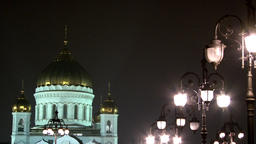 People walk along Patriarchal bridge to Cathedral of Christ Savior at night Footage