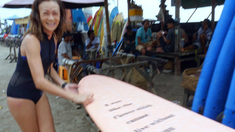 SUrfer Asian woman smiling happy applying wax to her surfboard beafore surfing 영상물