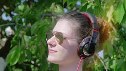 Beautiful teenage girl with headphones enjoys music GIF