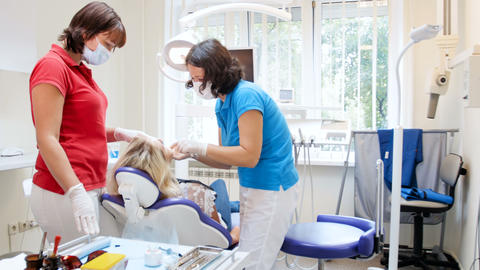 4k video of dentist with nurse treating young woman sitting in dental chair Footage