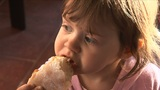 Little Girl Eating Bread stock footage
